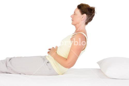 Side view of mature woman exercising on bed