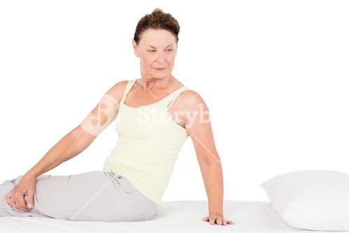 Confident mature woman exercising on bed