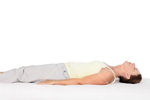 Side view of woman exercising on bed