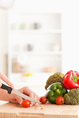 Womans hands slicing tomatoes
