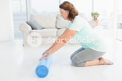 Mature woman rolling exercise mat