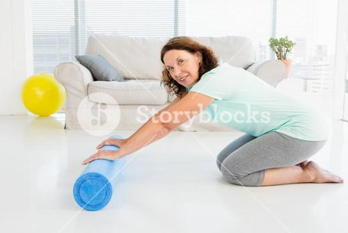 Portrait of smiling mature woman rolling exercise mat