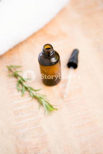High angle view of aromatherapy oil bottle by rosemary