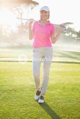 Portrait of cheerful woman carrying golf club