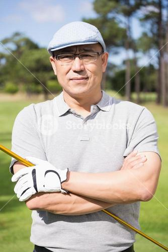 Portrait of happy golfer with arms crossed