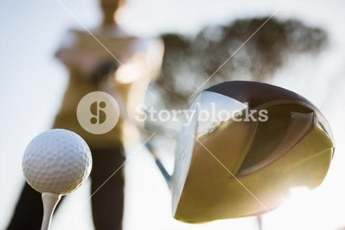 Focus on foreground of golf club and ball