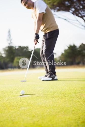 Focus on foreground of golf ball and a hole