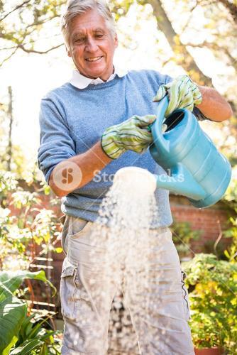 Happy gardener watering plants at garden