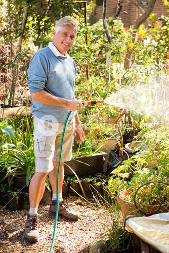 Portrait of gardener watering plants from hose at garden
