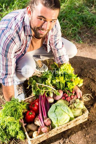 Portrait of happy gardener crouching with vegetables at garden
