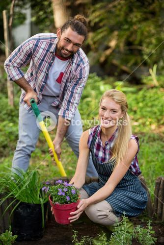 Portrait of happy gardeners with potted plant and shovel at garden