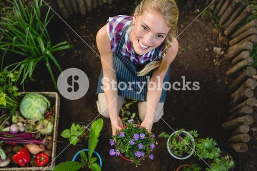 Portrait of happy gardener with potted plant at garden