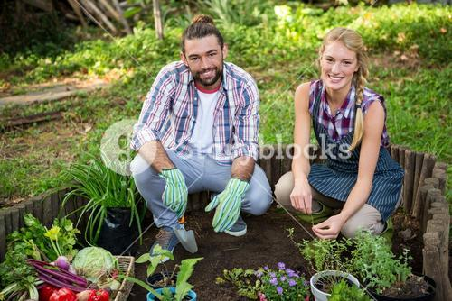 Portrait of happy gardeners with potted plants at garden