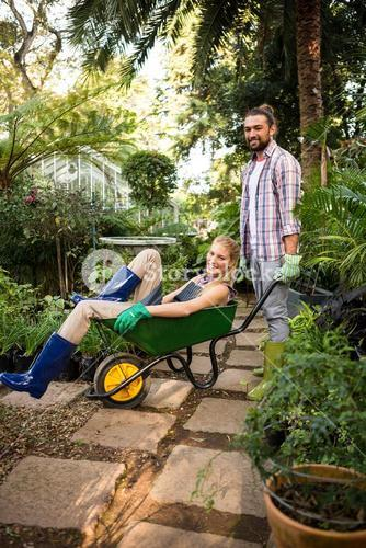 Portrait of cheerful colleagues enjoying with wheelbarrow at garden