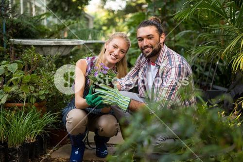 Portrait of happy colleagues holding potted plants at garden