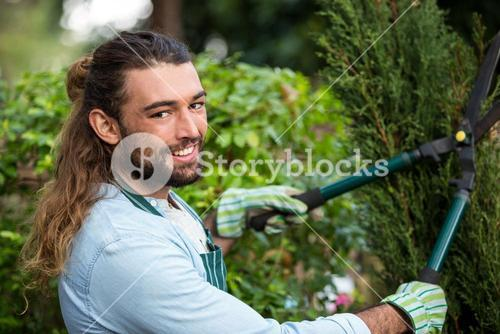 Portrait of confident gardener with hedge clippers at garden