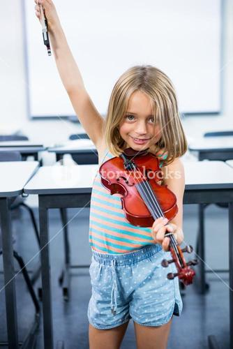 Happy girl playing violin in classroom