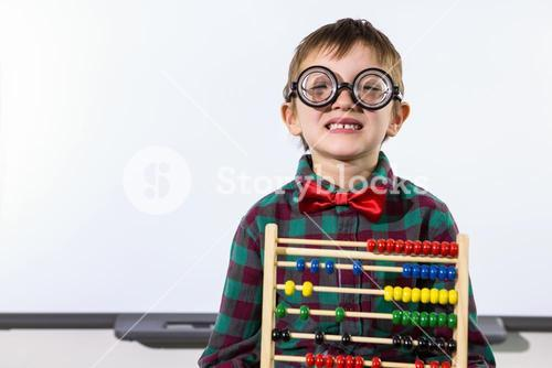 Cute boy with abacus against whiteboard in classroom