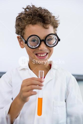 Cute boy holding test tube with liquid at laboratory