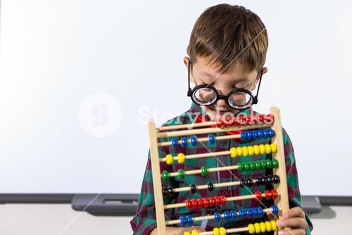 Cute boy playing with abacus in classroom