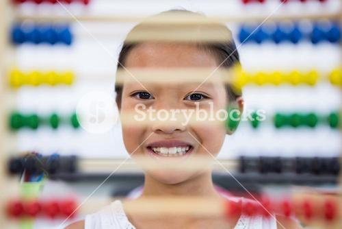 Girl in front of abacus in classroom