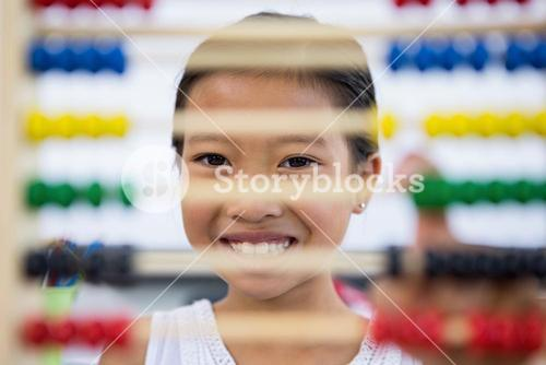 Smiling girl in front of abacus in classroom