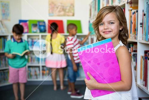 Portrait of girl holding books in school library