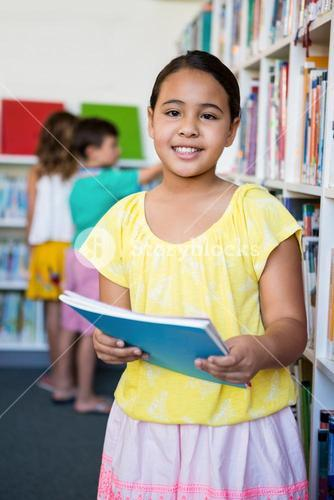 Elementary girl holding books in school library