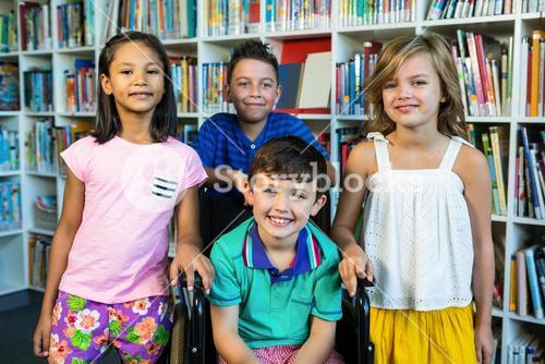 Handicapped boy with friends at library in school