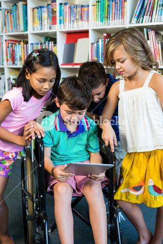 Handicapped boy holding digital tablet with friends at library
