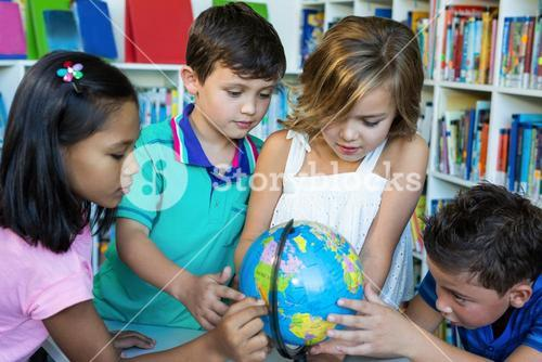 Students looking at globe in school library