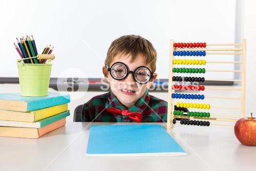 Boy with books and abacus in classroom