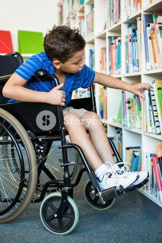 Handicapped boy searching books at library