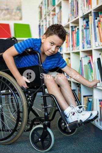 Portrait of handicapped boy searching books in library