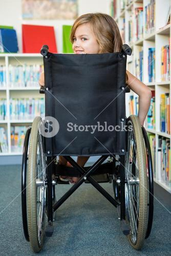 Rear view of handicapped girl at school library