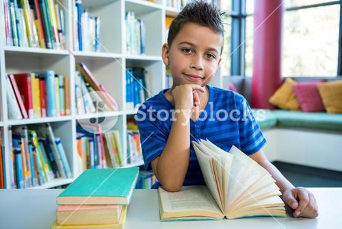 Boy reading book at table in school library
