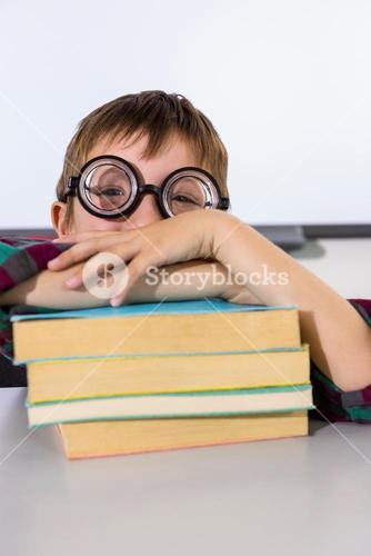 Boy leaning on books at table in classroom