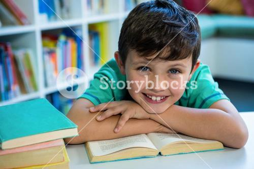 Smiling boy with book in school library