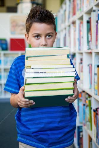 Boy holding books in school library