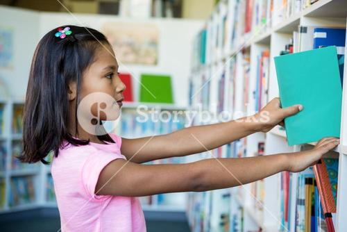 Girl searching books in school library
