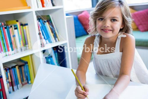 Smiling girl studying in school library