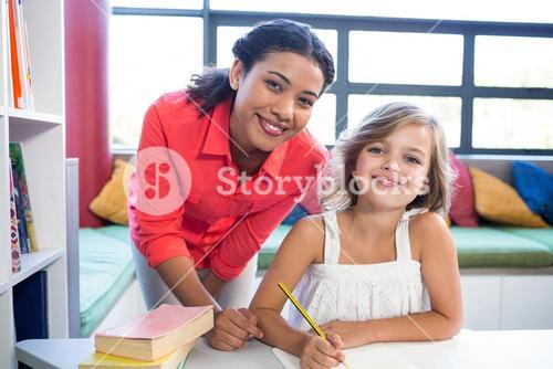 Portrait of teacher with girl in school library