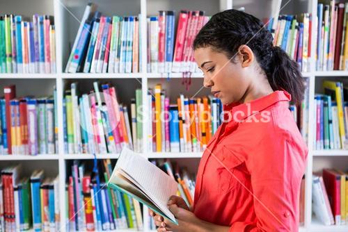 Teacher reading book at library in school