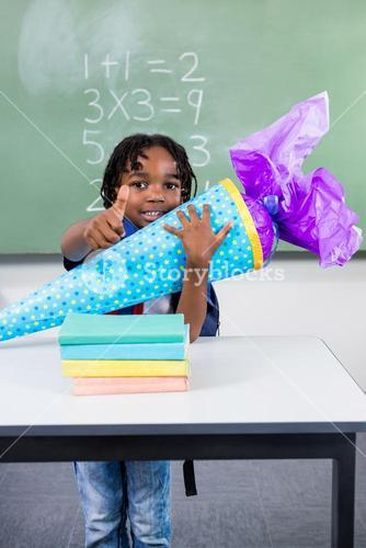 Boy holding gift at table in classroom