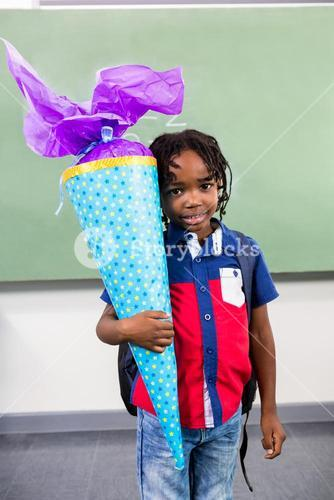 Boy holding gift against board in classroom