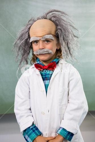 Portrait of boy dressed as scientist standing against board
