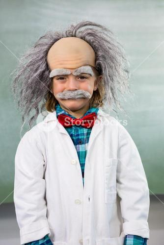 Smiling boy dressed as scientist standing against board
