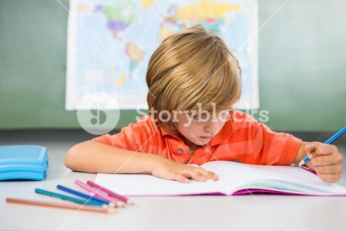 Boy writing on book in classroom