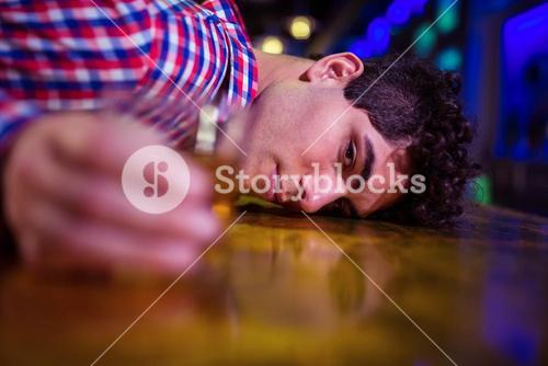 Portrait of drunk man at bar counter