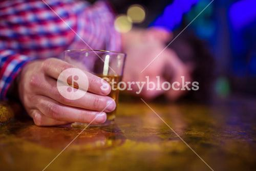 Man with whiskey glass lying on bar counter